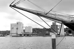 Bugspriet eines historischen Seglers im Flensburger Museumshafen - Blick über die Förde zu Siloanlagen / Industrieanlagen im Hafen von Flensburg.
