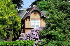 Villa / Einzelhaus im Grünen, blühender Goldregen und Rhododendron zwischen Bäumen - Klinkerfassade mit Schnitzwerk im Hausgiebel in Flensburg.
