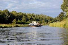 Morgenstimmung auf dem Salzstraße Elbe-Lübeck-Kanal hinter Mölln, ein Binnenschiff fährt zwischen den Bäumen.