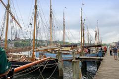 Historische Segelschiffe liegen am Holzsteg im Museumshafen von Flensburg.