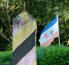 Alter Betongrenzpfeiler mit den Farben  Schwarz Rot Gold in Barhöft - im Hintergrund eine polnische Flagge.