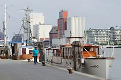 Boote am Kai im Flensburger Hafen nahe der Schiffbrücke - im Hintergrund Silos und Wohngebäude am Fördeufer.