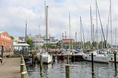 Foto aus dem Flensburger Hafen, Marina mit Segelschiffen beim Strandweg - im Hintergrund das Kraftwerksgelände und der hohe Schornstein der Flensburger Stadtwerke.