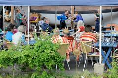 Eine Musikgruppe spielt im Werftcafé von der Museumswerft Flensburg.