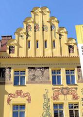 Hausfassade mit Treppengiebel - aufwändige farbige Bemalung auf gelbem Grund - Gebäude in der Straße Veleslavínova von Pilsen / Plzeň.