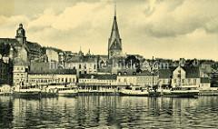 Alte Fotografie vom Hafenrand in Flensburg - Fahrgastschiffe liegen am Kai; Blick zur  Marienkirche und dem Uhrenturm vom Alten Gymnasium.