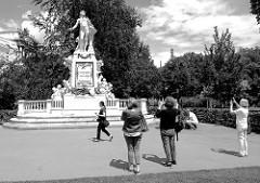 Touristinnen fotografieren das Mozart-Denkmal im Burggarten von Wien.  Das Denkmal wurde 1896 eingeweiht - Entwurf / Umsetzung  Architekt  Karl König und  Bildhauer Viktor Tilgner.