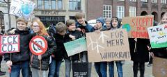 Fridays for Future - Demo in Hamburg - 01.03.2019. Treffpunkt der DemonstrantInnen auf dem Hamburger Gänsemarkt  - Schilder mit den Forderungen / Slogans: Für mehr Windkraft - Stoppt den Klimawandel.