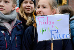Fridays for Future - Demo in Hamburg - 01.03.2019. Eine Demonstrantin auf dem Gänsemarkt träg ein  Schild mit Friday for Future.