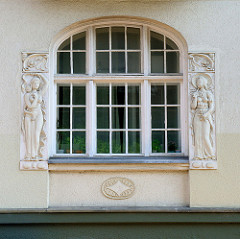 Fenster mit figürlichem Reliefschmuck, denkmalgeschütztes Wohnhaus am Nordergraben in Flensburg.