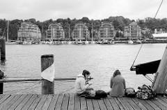 Entspannung auf dem Holzsteg im Museumshafen von Flensburg - Touristinnen machen eine Pause am Wasser der Flensburger Förde; am gegenüber liegenden Ufer eine Marina mit Sportbooten und Neubauten Ballastkai.