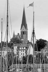 Blick durch die Masten von Segelschiffen über die Flensburger Förde zur Sankt Jürgen Kirche auf dem Jürgensbyer Hügel.