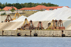 Schüttgut und abmontierte  Krangreifer / Zweischalengreifer am Hafenkai  an der Trave in Lübeck Herrenwyk.