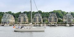 Ein Segelschiff fährt in den Flensburger Hafen ein - am gegenüberliegenden Ufer Neubauten mit Blick auf das Wasser.