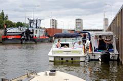 Sportboote und ein Schubschiff mit einem beladenen Containerleichter liegen in der Schleusenkammer der Schleuse Geesthacht an der Elbe.