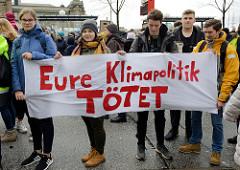 SchülerInnen halten ein handgemaltes Transparent mit der Aufschrift: Eure Klimapolitik TÖTET. Fast 10 000 SchülerInnen protestieren am 15.03.2019 bei der Fridays for Future-Demonstration in Hamburg für mehr Klimaschutz