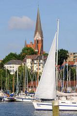 Blick über die Flensburger Förde zur Sankt Jürgen Kirche auf dem Jürgensbyer Hügel;  Ein Segelboot fährt Richtung Ostsee.