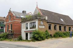 Wohnhäuser in der Schlossallee von Glücksburg / Ostsee. Gebäude mit gelber Ziegelfassade und Vorbau für Geschäftsraum mit Dachterrasse.