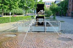 Wasserspiel - Fontänenbrunnen an der Nikolaistraße in Flensburg - dahinter das  Mühlenstrom-Wasserrad; errichtet 1998 - Entwurf Uwe Appold.