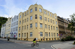Schlichte Jugendstilarchitektur in Karlsbad /  Karlovy Vary - mehrstöckige Wohngebäude / Eckgebäude mit floralem Stuckdekor und halbrunden Giebeln.