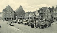 Historische Fotografie vom Flensburger Südermarkt. Eine Straßenbahn hält an einer Haltestelle - Marktstände sind aufgebaut, ein KFZ mit Anhänger steht am Strassenrand.
