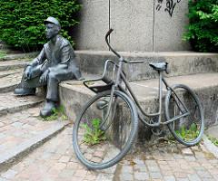 Postbotenstatue / Skulptur eines Briefträgers in Uniform mit Postmütze und Fahrrad am Postbankcenter in der Bahnhofstraße von Flensburg.