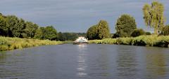 Morgenstimmung auf dem Elbe-Lübeck-Kanal hinter Mölln, ein Binnenschiff fährt zwischen den Bäumen.