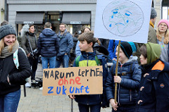 Fridays for Future - Demo in Hamburg - 01.03.2019 . Demonstranten auf dem Gänsemarkt tragen Demoschilder mit dem Slogans: Warum lernen ohne Zukunft / weinende Erde.