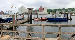 Station der Wasserschutzpolizei  im Flensburger Hafen - Polizeiboote unterschiedlicher Größe liegen am Steg, in der Bildmitte ein  Pegelhaus.