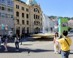 Sprudel, Springbrunnen / Vřídlo an der Straße Vřídelní in Karlsbad /  Karlovy Vary. Im Hintergrund das Jugendstilgebäude der Stadtsparkasse - eröffnet 1906 - Architekt Otto Stainl.