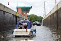 Sportboote und ein beladenes Binnenschiff verlassen die Schleusenkammer des Elbe-Lübeck-Kanals bei Lauenburg.