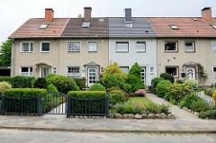 Einstöckige Reihenhäuser an der Twedter Mark in Flensburg; schmale Wohneinheiten mit unterschiedlicher Vorgarten- und Fassadengestaltung.