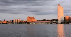 Abendstimmung am Hafen / Ziegelsee von Mölln - die untergehende Sonne scheint rötlich auf die Silos und Speichergebäude am Hafenrand.