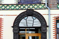 Eingang mit geschnitztem Holzportal / Putten - Architekturbilder aus Flensburg.