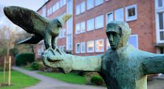 Skulptur Der Falkner im Hamburger Stadtteil Uhlenhorst - ein Falkner auf einem Pferd hält den Falken mit ausgebreiteten Flügeln auf dem Falknerhandschuh.