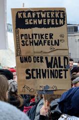 Pappschild  mit der Aufschrift: Kraftwerke schwefeln, Politiker schwafeln und der Wald schwindet.   Fast 10 000 SchülerInnen protestieren am 15.03.2019 bei der Fridays for Future-Demonstration in Hamburg für mehr Klimaschutz.