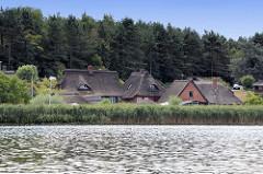Blick von der Trave auf Reetdachhäuser der Fischersiedlung Gothmund / Hansestadt Lübeck.