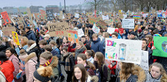 Fridays for Future - Demo in Hamburg - 01.03.2019 .DemonstrantInnen tragen Demoschilder mit den Forderungen / Slogans: Die Zeit läuft, wir wollen auch eine Zukunft - Kohle in die Bildung statt in den Ofen.