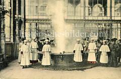 Quelle / Sprudel in Karlsbad - Weiße Colonnaden -  alte Fotografie mit Kurgästen und angestellten Frauen in weißen Kleidern, die das Heilwasser aus der Quelle schöpfen.