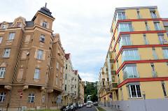 Alt und Neu - historisches mehrstöckiges Wohnhaus mit Eckerker und Turm im Baustil der Gründerzeit gegenüber eines mit roten Streifen und Glaserker versehener Neubau in der Straße K. Čapka in Karlsbad /  Karlovy Vary,