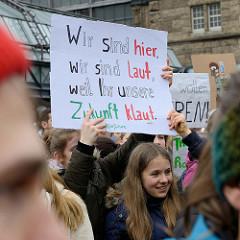 Handemalte Schilder u. a. mit der Aufschrift: Wir sind hier, wir  sind laut, weil ihr unsere Zukunft klaut.   Fast 10 000 SchülerInnen protestieren am 15.03.2019 bei der Fridays for Future-Demonstration in Hamburg für mehr Klimaschutz.
