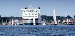 Das Fährschiff Nils Holgersson verlässt auf der Trave das Lübecker Terminal und fährt auf der Höhe Travemündes in die Ostsee ein.