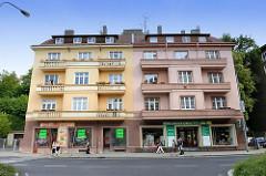 Wohn- und Geschäftshaus in der Straße Vítězná von Karlsbad /  Karlovy Vary. Die Fassaden des mehrstöckigen Doppelgebäudes haben eine unterschiedliche Fassadenfarbe - die Balkons haben teilweise noch eine Säulenbrüstung.