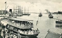 Alte Luftansicht vom Hafen in Flensburg - Frachtsegler liegen am Kai, dicht besetzte Fahrgastschiffe verlassenen den Anleger.