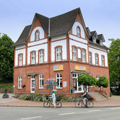 Historische Architektur in Glücksburg / Ostsee - Ziegelgebäude mit teilweise weißer Putzfassade - Uhr im Giebel.
