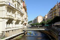 Der Fluss Teplá verläuft durch den Badeort Karlsbad /  Karlovy Vary; mehrstöckige Gründerzeitarchitektur steht entlang des Flusslaufes im Zentrum der Stadt.