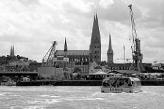 Blick von der Trave zu Hafenanlagen im Lübecker Hafen - im Hintergrund die Kirchtürme der Hansestadt.