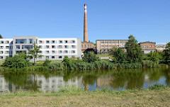Neubau eines Seniorenwohnheimes am Ufer der Radbuza in Pilsen / Plzeň - dahinter Werksgebäude einer stillgelegten Fabrik.