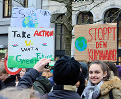Fridays for Future - Demo in Hamburg - 01.03.2019 . DemonstrantInnen auf dem Gänsemarkt tragen ein  Demoschild mit den Forderungen: Stoppt den Klimawandel - Take Action, we  want a green future.