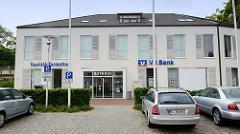Schlichtes Verwaltungsgebäude, Sitz vom Rathaus Glücksburg (Ostsee), der Touristeninformation und einer Bank.